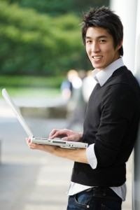 A shot of an asian student working on his laptop at the campus